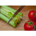 Green stalks of celery and red tomatoes on a wooden cutting board beside an iron knife 64239