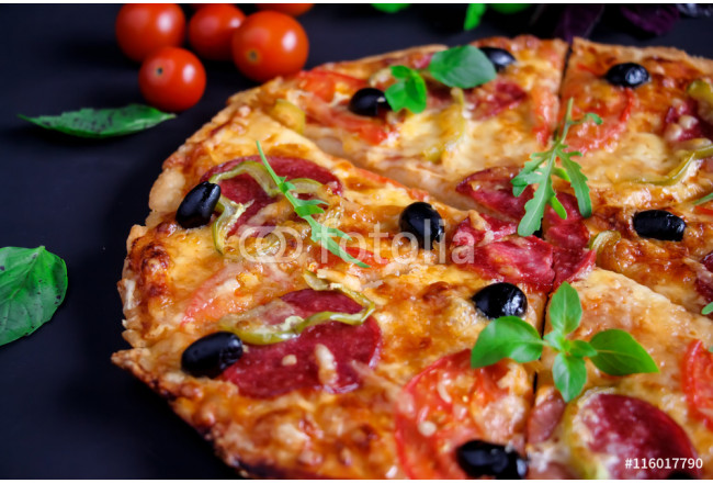 Homemade pizza with salami, black olives and basil. 64239