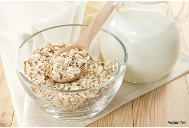 Oat flaks on a glass bowl and jug of milk 64239