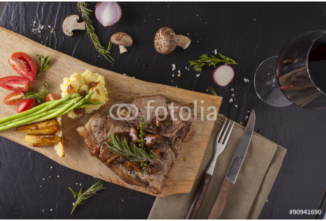 T-bone steak, a prepared piece of grilled T-bone steak brown sauce with mashed potato and vegetable on dining table decorated 64239