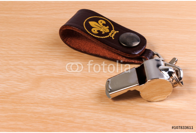 Obraz nowoczesny Metal whistle with leather keychain on wooden background. 64239