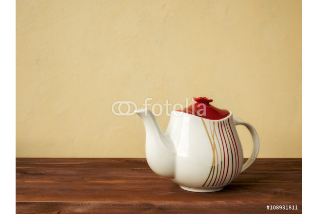 White teapot standing on the wooden table 64239