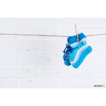 knitted baby socks hanging on clothesline against white brick wa 64239