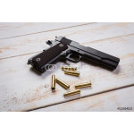 hand gun with rounds on wooden desk 64239