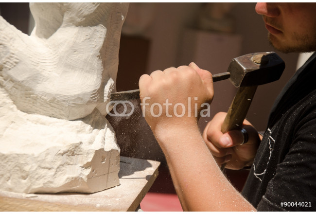 Man with hammer working on stone statue 64239
