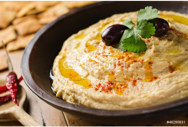 A bowl of creamy hummus with olive oil and pita chips. 64239