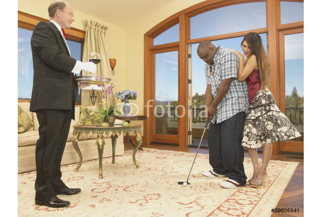 Couple playing golf in house with servant watching 64239