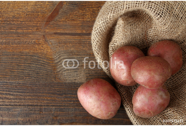 red potatoes on burlap on wooden brown background 64239