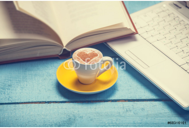 Cup of coffe with laptop and book on blue wooden table. 64239