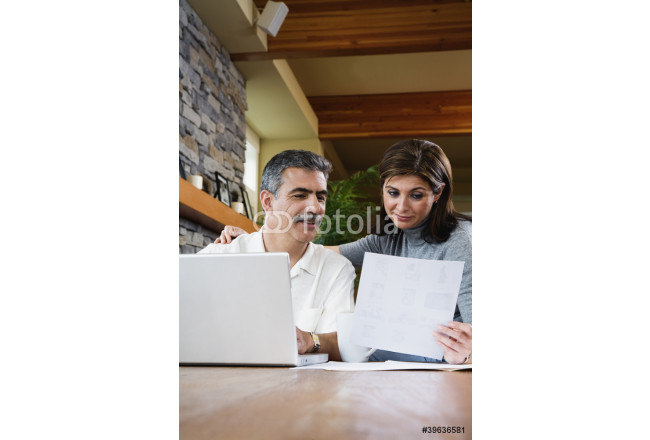 Middle-aged couple looking at paperwork and laptop 64239