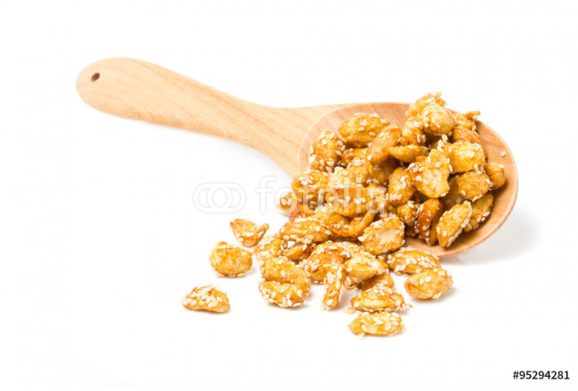 Crispy sugared nuts with wooden spoon isolated on white. 64239