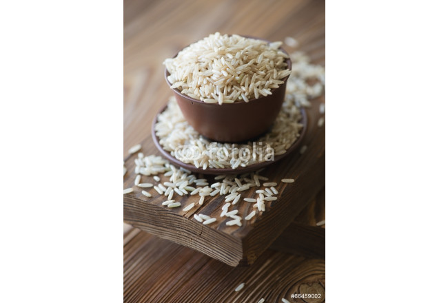 Raw brown rice over rustic wooden background, close-up 64239