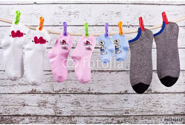 Socks family of four dried on the clothesline on wooden background painted walls 64239
