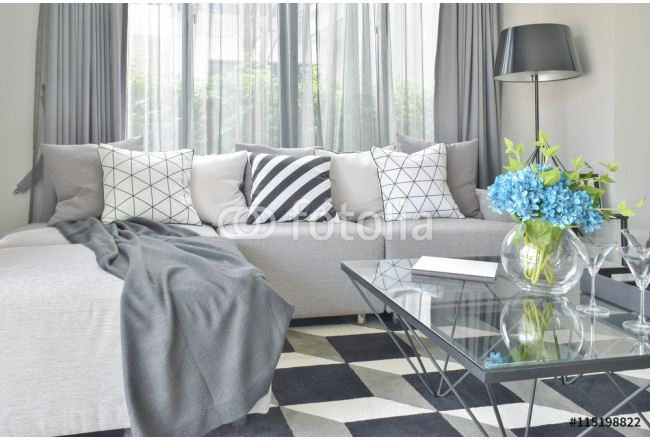 Light gray L shape sofa set with varies pattern and color pillows in modern living room 64239