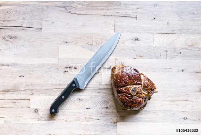 beautiful grilled slice of an organic leg of lamb meat with a kitchen knife on a oak tree cutting board seen from above 64239
