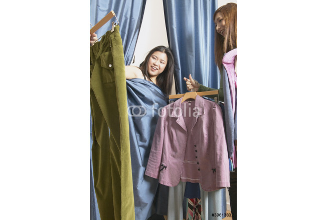 Woman covered with curtain from dressing room looking at clothes 64239