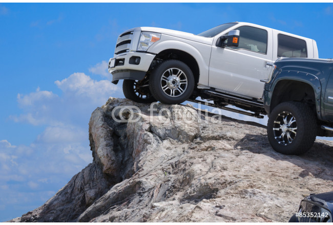 Big rugged trucks on the edge of a rocky cliff ledge 64239