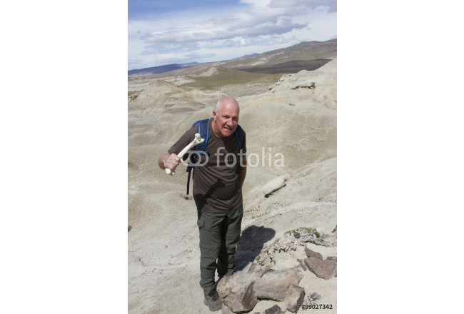 Man posing with guanaco bone standing over fossilized dinosaur bones in La Leona Petrified Forest, Argentina. 64239
