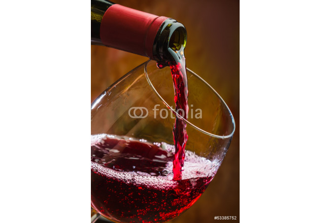 Wine pours into the glass of the bottle 64239