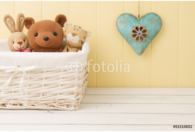 Stuffed animal toys in a basket on the floor and a blue heart on the wainscot 64239