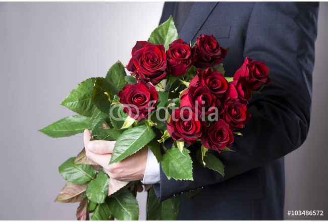 Man with bouquet of red roses on a gray background 64239