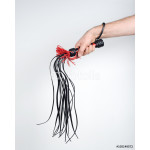 Man's hand holds a whip (flogger). 64239