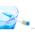 toothbrush and toothpaste in blue plastic glass 64239