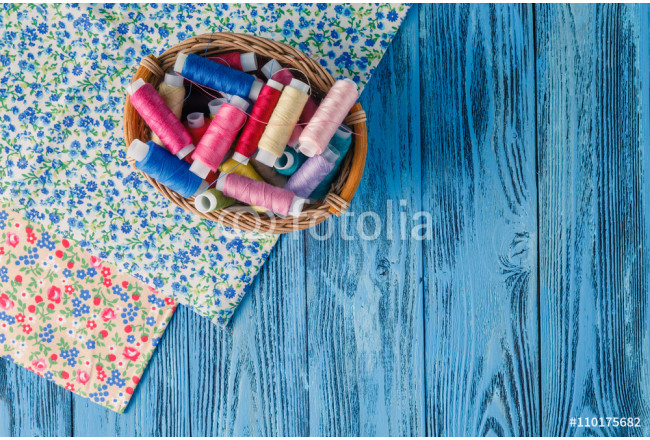 Obraz nowoczesny Colored sewing threads on a old work table 64239
