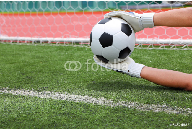Goalkeeper's hands catching soccer ball over the line of goal wi 64239