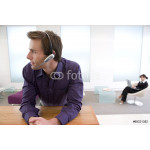 Businessman with headset, colleague in background 64239