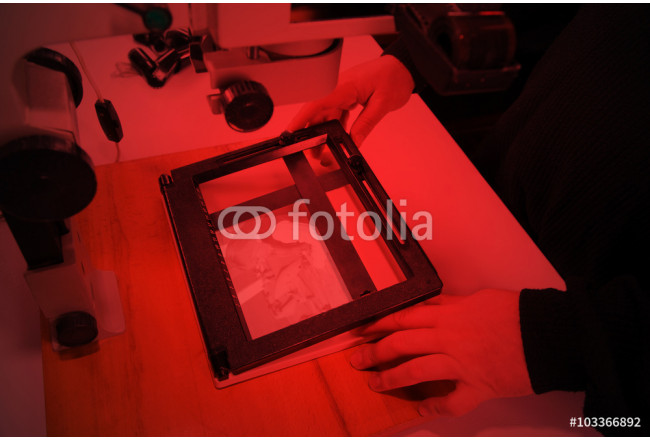 Photographer in the laboratory with  enlarger projects the image from a negative on photo paper 64239
