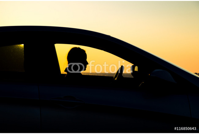 Obraz nowoczesny Silhouette of sedan car with girl on the background of beautiful sunset 64239
