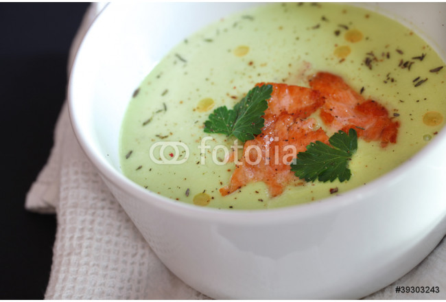 Avocado soup with fried salmon slices in a white soup bowl 64239