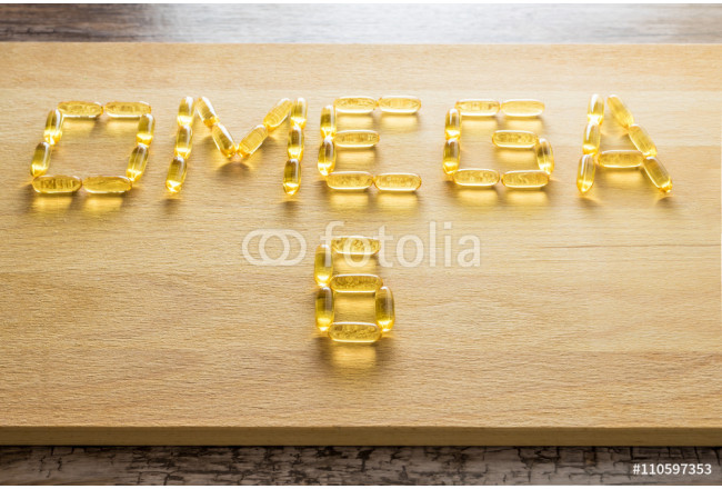 Omega 3-6-9 fish oil yellow softgels drawing omega 6 letters on wooden board on rustic table. 64239
