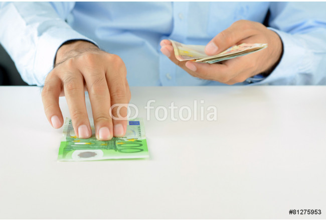 Hand giving (pushing) money, Euro currency (EUR), on white desk 64239