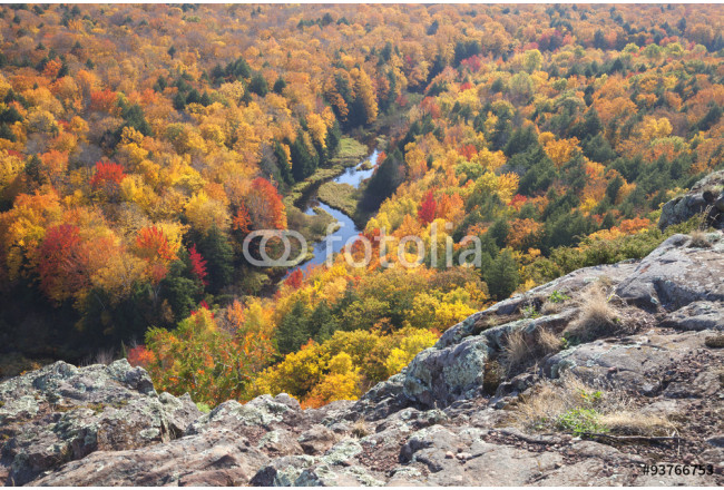 Trees in full autumn color and a small river viewed from rocky o 64239