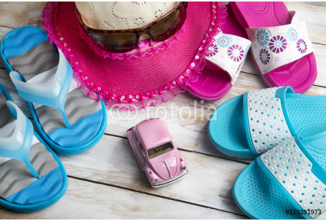 Pair of slippers and pink straw hat on wood. Vacation in summer 64239