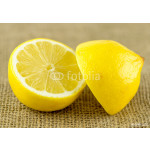 Unpeeled lemon cut in half with bright yellow rind 64239