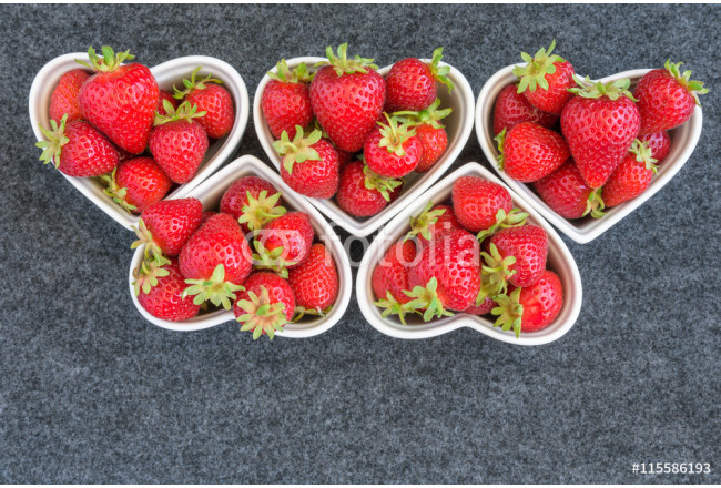 Fresh picked strawberries in white heart shaped bowls, on a gray background