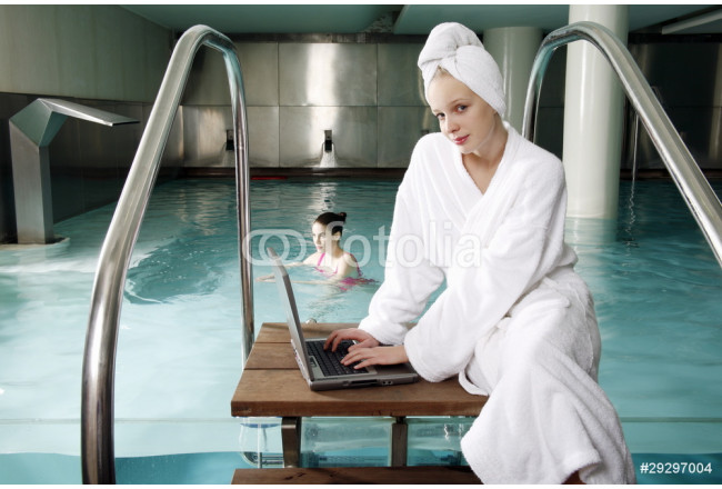 Woman on computer next  to a swimming pool 64239