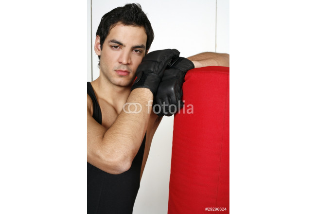 Young man leaning on punching bag 64239