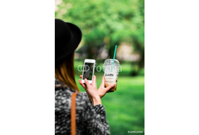 beautiful and young girl with a coffee in stylish hat taking photos on own phone, on nature for social networks. selfie. background 64239