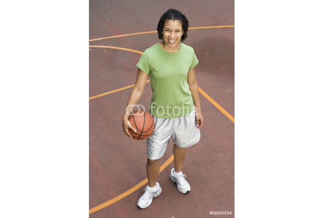 Portrait of teenage girl with basketball on court 64239
