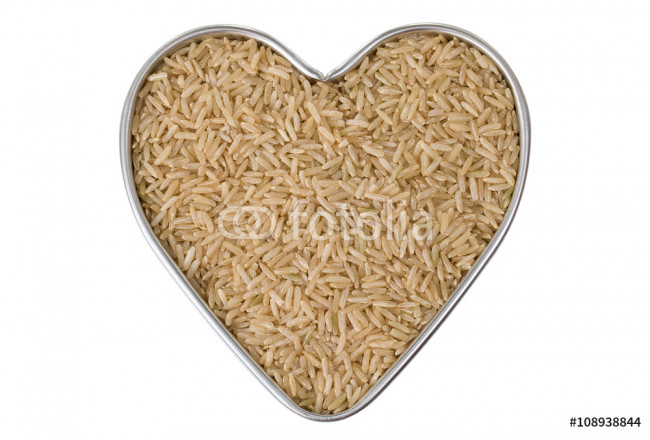 Heart shaped tin pan full of raw Thai half polished Brown Jasmine rice grains, isolated on white background.  64239