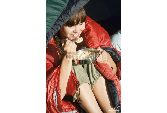 Bild auf Leinwand Young woman, wrapped in red sleeping bag, sitting in tent on camping trip, eating cereal, smiling, close-up 64239