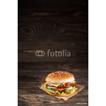 tasty Cheese burger with grilled meat, cheese, tomato, on craft paper on wooden surface. Fast food template. 64239