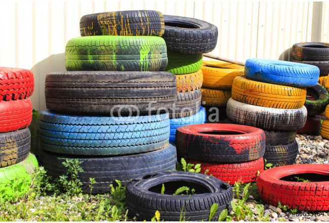 colorful waste tires towers. dump waste of colored tires of different sizes 64239