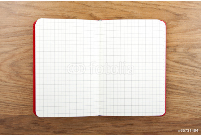 Notebook with square grid on wooden table. 64239