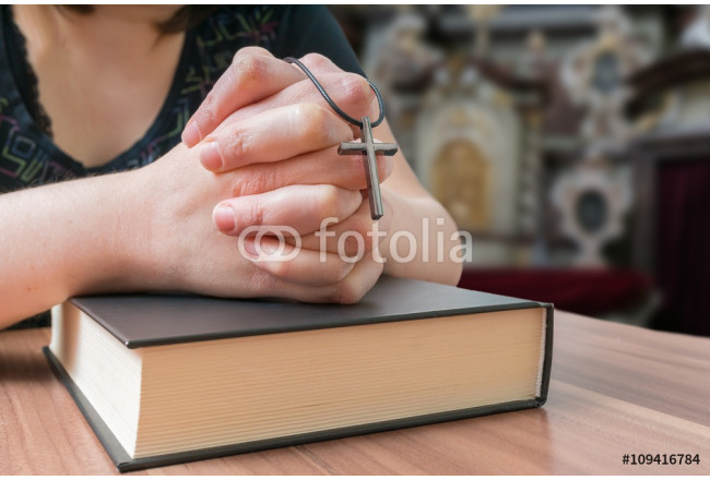 Praying woman holds cross in church. 64239