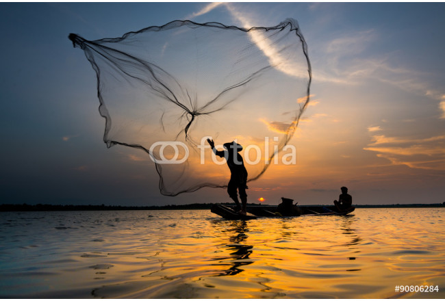 Silhouette of a fisherman throwing his net with sunset. 64239
